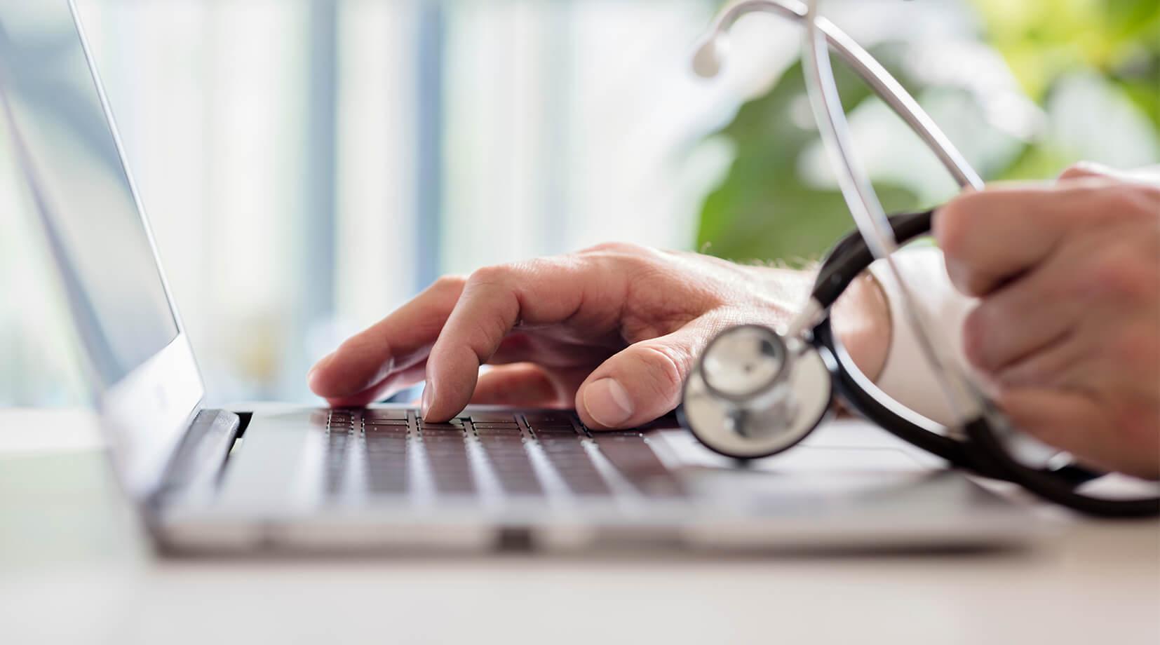 Doktor ze stetoskopem pracujący przy komputerze