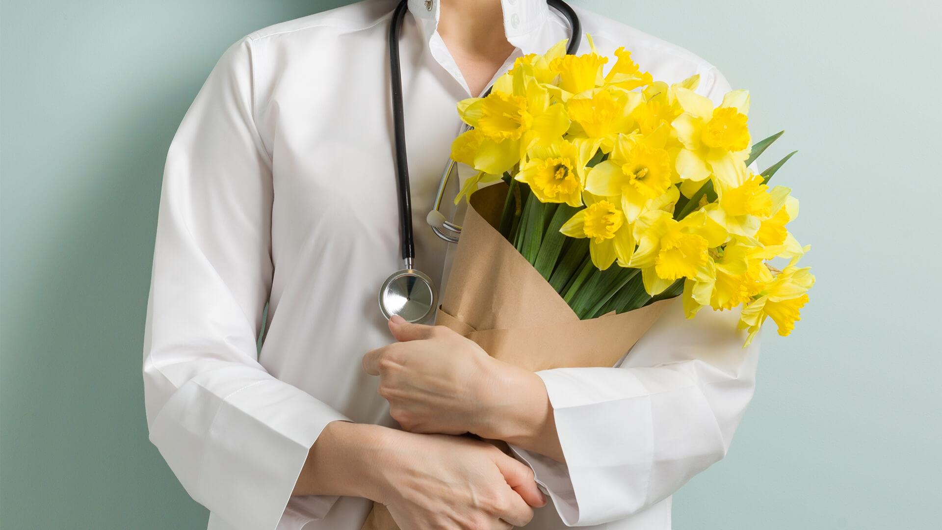 Zdrowych i radosnych Świąt Wielkanocnych - lekarka z bukietem kwiatów